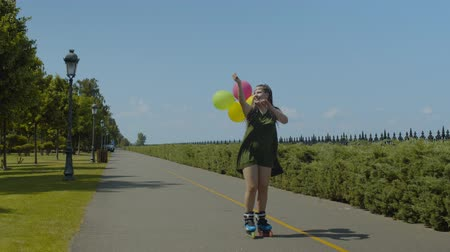 inline skating : Cheerful female with hairstyle from afro-braids holding colorful balloons while rollerskating in well-kept public park. Young smiling woman roller enjoying outdoor summer leisure on roller blades.