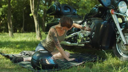 İngiliz anahtarı : Stylish independent woman biker with tatoo fixing broken motorbike using tools and wrenching nut on park lawn. Attractive short cut female rider with wrench repairing motocycle outdoors on summer day.