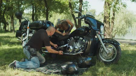İngiliz anahtarı : Brutal male biker helping pretty woman to repair broken motorcycle and teaching her which wrench to use during maintenance outdoors. Experienced man giving advice on repair to woman biker on park lawn Stok Video