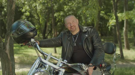 байкер : Outdoor lifestyle portrait of cheerful man biker in leather jacket holding steering wheel while sitting on custom motorcycle. Positive motorcyclist looking with friendly smile before ride on motorbike Стоковые видеозаписи