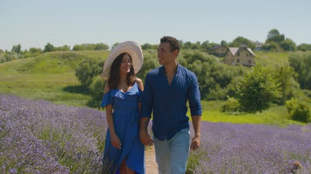 sunhat : Stylish smiling lovely woman in sunhat and sundress and handsome mixed race man holding hands enjoying walk in purple lavender field. Cheerful mixed race couple spending leisure in countryside.