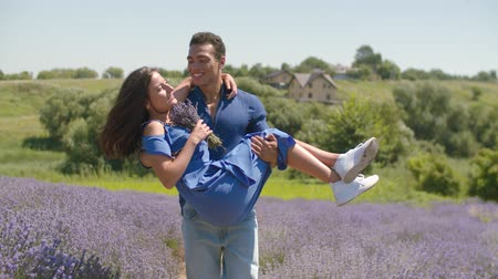 lavanda : Affectionate handsome african american man carrying charming woman with bouquet of fresh lavender flowers in his arms during a walk in lavender field. Loving mixed race couple enjoying outdoor leisure