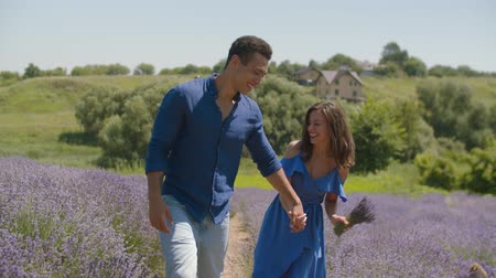 piada : Excited carefree multiracial couple in love holding hands, having fun and fooling around while walking in blooming lavender field. Playful couple enjoying freedom and summer nature in countryside.