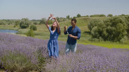 lavender field : Excited carefree multi ethnic couple playing with soap bubbles in lavender field on summer vacations. Positive joyful mixed race couple having fun, blowing soap bubbles and enjoying summer nature. Stock Footage
