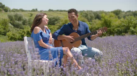 serenade : Loving african american man playing acoustic guitar and singing love song to pretty woman in lavender field. Positive mixed race couple playing guitar while enjoying romantic date in summer nature