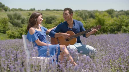 akusztikus : Romantic handsome dark-skinned man serenading his charming beloved woman with acoustic guitar in lavender field. Affectionate mixed race couple playing guitar on romantic date in summer nature.