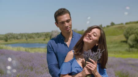 букет : Charming elegant woman with loving mixed race man enjoying fresh fragrant lavender blossoms during summer vacations. Pretty joyful female inhaling aroma of blooming lavender flowers in countryside.