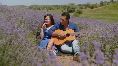 lavender field : Carefree diverse couple enjoying romantic picnic in blooming lavender field on summer vacations. Positive black guy playing guitar serenading his charming woman sipping red wine during romantic date.