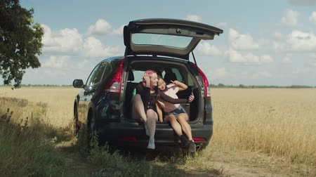 diverso : Carefree excited multiethnic young women taking selfie shot on smart phone in car trunk. Positive diverse girlfriends posing for selfie, making funny faces and expressions during summer road trip. Stock Footage