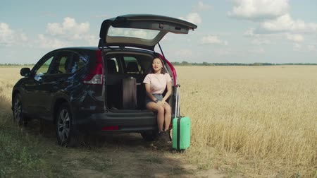 časová prodleva : Impatient young asian woman with suitcases sitting in car trunk, checking the time on wrist watches, being nervous and stressed while waiting her friend, being late for summer vacations road trip.