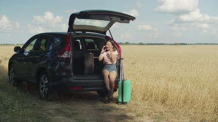 časová prodleva : Angry impatient asian young woman with suitcases sitting in car trunk, checking the time and calling on phone to friend being late for summer vacations road trip, expressing anxiety and disappointment