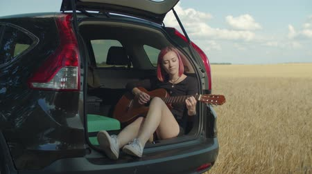 outdoor hobby : Dreamy hipster woman playing acoustic guitar sitting in open car trunk during summer vacations road trip. Charming female with guitar enjoying outdoor leisure while travelling by car in countryside.