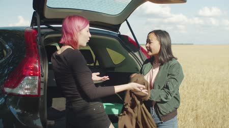 dispute : Multiethnic female friends packing for road trip, emotionally discussing needfulness of packed things into luggage near car trunk, throwing away stuffs while preparing for summer vacations travel.