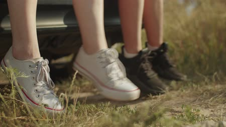 human foot : Close-up of womens legs in trendy sneakers dangling from car trunk during summer vacations road trip in countryside. Joyful female travelers enjoying outdoor leisure and freedom during car trip. Stock Footage
