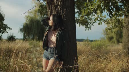 alluring : Stunning charming asian young woman leaning on tree, enjoying outdoor leisure in rays of beautiful sunset in countryside, looking with warm smile, expressing alluring innocent female beauty in summer. Stock Footage