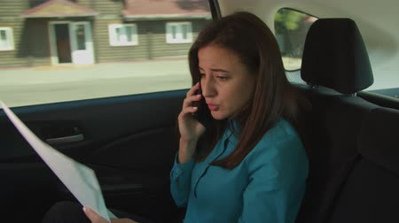 gidermek : Annoyed female business executive analyzing sale reports and documents, displeased by financial datas and resolving problems on cellphone while riding on backseat of car during business travel. Stok Video