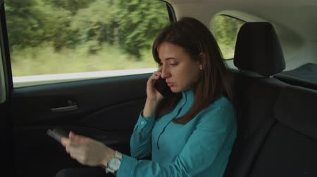 remotely : Successful multitasking female entrepreneur in formal wear discussing business ideas with colleagues on smart phone, browsing online with tablet pc while traveling to meeting on back seat of car. Stock Footage