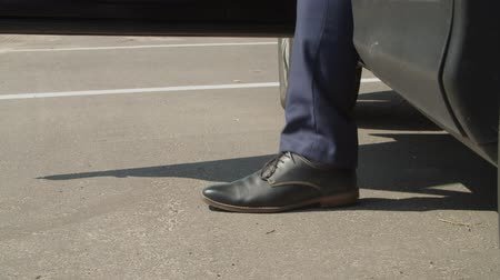 exiting : Close-up of male legs in elegant black shoes and suit exiting parked luxury car. Low section of wealthy businessman in trendy suit and shoes getting out of parked vehicle and walking away. Stock Footage