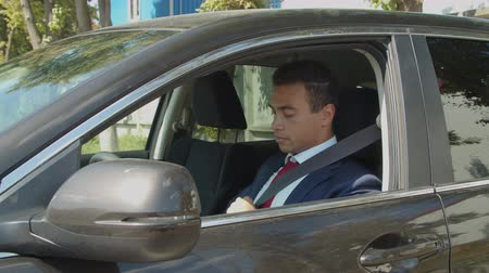 belting : Handsome confident african american businessman in formalwear sitting in drivers seat and fastening seat belt before driving. Serious mixed race entrepreneur adjusting security belt in modern car. Stock Footage