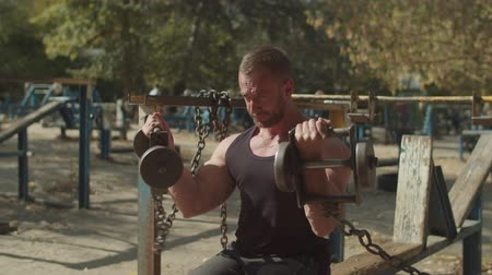 biceps curls : Muscular built handsome athlete working out at outdoor gym, sitting on weight training bench and doing bicep curls in seated position with two heavy dumbbells during sport training on fresh air. Stock Footage