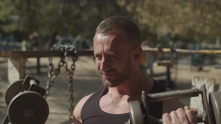 biceps curls : Portrait of confident muscular bodybuilder exercising with two dumbbells on fresh air while sitting on weight training bench. Determined fit athlete doing bicep curls in seated position at outdoor gym