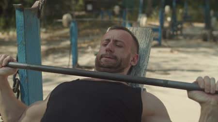 férfiasság : Portrait of concentrated bodybuilder working out barbell incline bench press in outdoor gym. Athletic man lifting barbell on incline bench and flexing chest muscles during sport training on fresh air.
