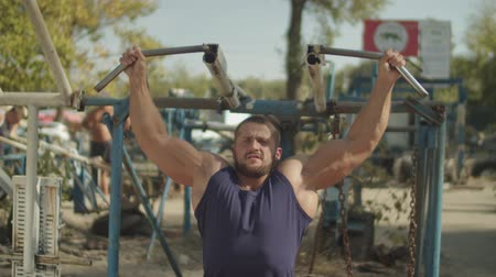 contra : Handsome motivated strong man working out using shoulder press machine in outdoors gym. Determined fit bodybuilder flexing chest and shoulder muscles on gym machine during outdoor training.