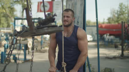 equipamentos esportivos : Confident strong muscular built man doing pushdown on cable machine in outdoor gym. Athletic fit handsome bodybuilder exercising triceps pushdown at the rope cable machine during outdoor workout.