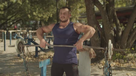 gewichtheffer : Muscular male bodybuilder working out in outdoor gym doing exercises with barbell. Athletic fit man performing upright -row weigth training exercise, lifting barbell straight up to collarbone outdoors