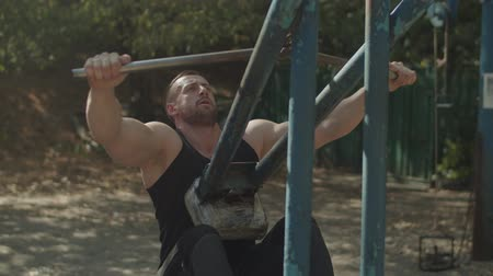 contra : Handsome muscular bodybuilder exercising and flexing muscles on lat pulldown cable machine in outdoor gym. Strong fit man working out lat pulldown training upper body strength exercise for upper back.
