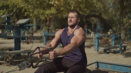 evezős : Concentrated confident fit man doing low pulley machine workout exercises in outdoor gym. Strong muscular bodybuilder practicing low cable pulley row seated while training on fresh air. Stock mozgókép