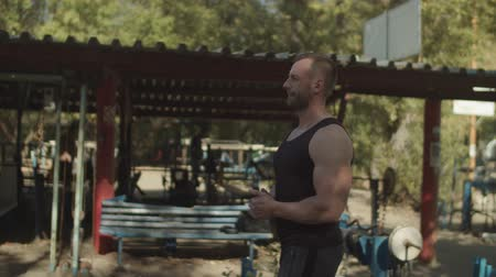 readiness : Strong well built bodybuilder with perfect abs, shoulders, biceps, triceps, chest getting ready for exercises during outdoor workout. Confident athletic fit man warming up muscles before training.
