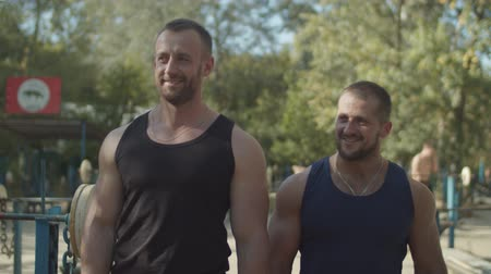 readiness : Portrait of two handsome brutal muscular bodybuilders communicating and walking along exercise machines before strength weight training in outdoor gym, expressing confidence and determination.