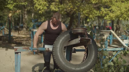downwards : Confident muscular bodybuilder making pushdown strength training for triceps using rustic exercise machine at outdoor gym. Athletic fit man doing triceps exercise while working out on fresh air. Stock Footage