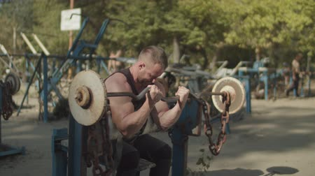 biceps curls : Handsome concentrated strong fit man performing barbell biceps curls while sitting on bench in outdoor gym. Determined muscular bodybuilder training and pumping up biceps with barbell outdoors.