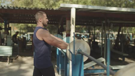 readiness : Determined motivated bodybuilder with well trained body warming up by stretching arm and shoulder muscles on the move in outdoor gym. Athletic fit man making warm up exercise for upper body outdoors.