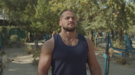 flexão : Serious motivated strong fit man flexing his muscles after sports training in outdoor gym. Confident muscular built bodybuilder showing his well trained body after intense outdoor workout. Stock Footage