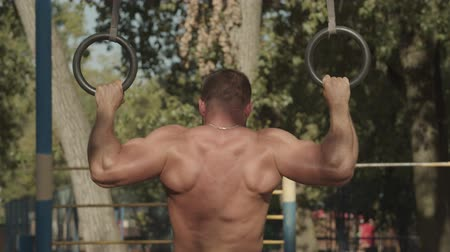 contra : Rear view of athletic muscular fit man with perfect body hanging and pushing up with gymnastic rings on outdoor sport facilities. Strong bodybuilder exercising outdoors with rings, doing pull-ups. Stock Footage