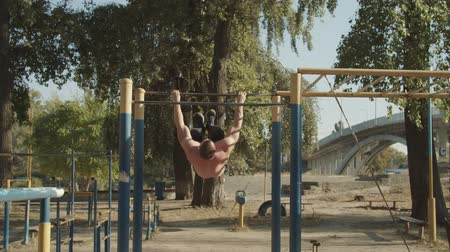 tornász : Shirtless motivated strong athlete with perfect trained body doing gymnastic exercises on crossbar while working out in outdoor gym at sunset. Muscular man training doing backflip on horizontal bar. Stock mozgókép