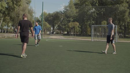 possession : Street soccer team players warming up, passing the ball during training session in the pitch on sunny day. Active young footballers exercising ball control, practicing on sports field before the match