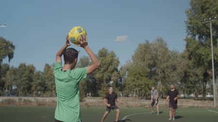 opponent : Rear view of young street soccer player taking throw-in and passing ball to teammates during football game on pitch. Offensive team returning to attack opponent goal after throw-in during soccer match