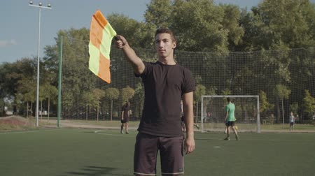 kural : Portrait of concentrated soccer assistant referee moving along touchline and signalling offside offence trap during football match. Linesman signals for offside by raising his flag during soccer game.