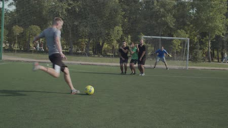 striker : Soccer player making direct free kick in attempt to score a goal during football game on pitch. Defending players forming wall to protect goal from free kick while playing soccer match on sports field Stock Footage