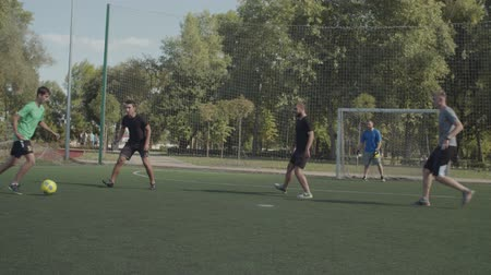 opponent : Positive street football players playing soccer game on the pitch in neighbourhood. Offensive team attacking opponent goal, striker taking a shot on goal and football goalie making a save during match
