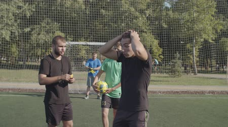 piłkarz : Portrait of frustrated soccer player cautioned by yellow card from referee during football match, walking on the pitch, expressing dissatisfaction, anger and disagreement with referee decision.