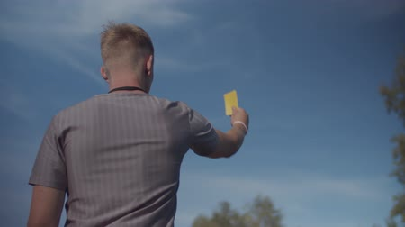 penas : Rear view of football referee indicating yellow card and warning offending player during soccer game over beautiful blue sky in background. Strict soccer referee showing penalty card during match. Stock Footage