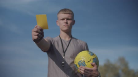 罰 : Serious football referee with soccer ball showing yellow card and warning offending player for foul during match. Portrait of determined soccer referee indicating yellow card to player during game.