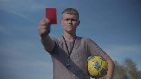 sertés : Strict football referee with soccer ball showing red card to send off offending player during game over blue sky background. Soccer referee showing red card indicating dismissal for match to player.
