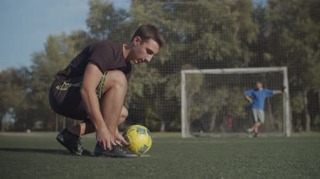 timeout : Low angle view of young soccer player tying shoelaces on sports shoes, getting ready to return playing game and passing the ball to goalie on the pitch during football match.