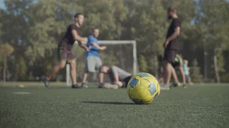fotbalista : Football team doing warm up exercises before soccer match. Foreground colorful soccer ball lying on the pitch with blurry football players warming up, practicing stretching exercises in background. Dostupné videozáznamy
